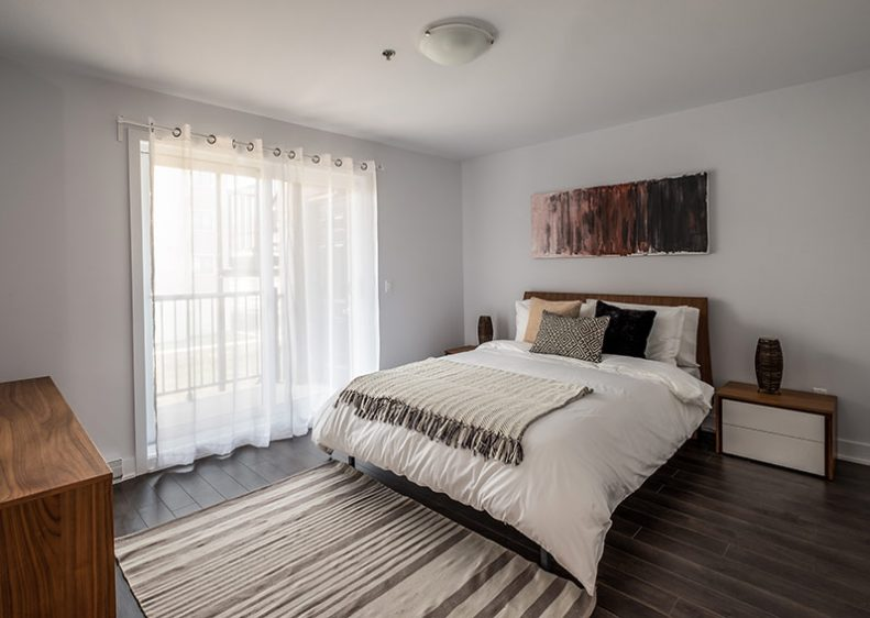 A spacious master bedroom with access to a private balcony