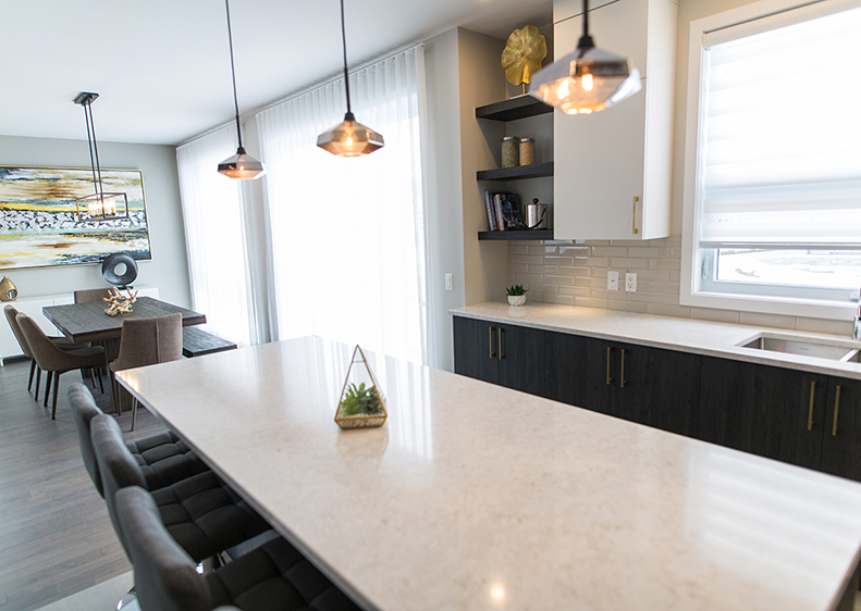 Modern kitchen and dining room space of our model home in Domaine du Parc