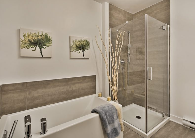 A spacious bathroom equipped with a glass shower and a majestic bath, ideal to relax in the evening